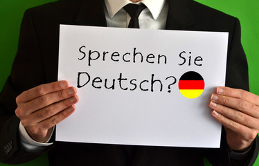Businessman showing a sheet with text Sprechen Sie Deutsch