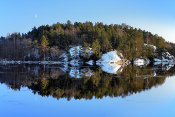 An island with pine trees reflected in the lake in winter