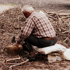 Vieil homme coupant du bois