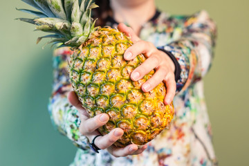 Fashion girl holding pineapple between her hands