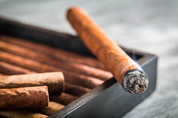 Burning cigar with smoke on wooden humidor
