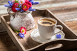 Coffee and spring flowers on wooden tray