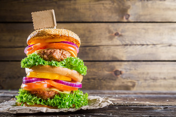 Double-decker burger on wooden background with space to menu