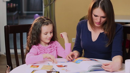 Happy mother teaches little daughter color book, learning colors