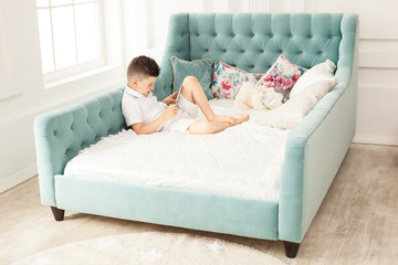 Young boy using tablet lying down on couch at home