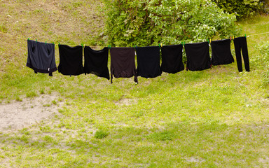 Black laundry hanging to dry on line outdoor