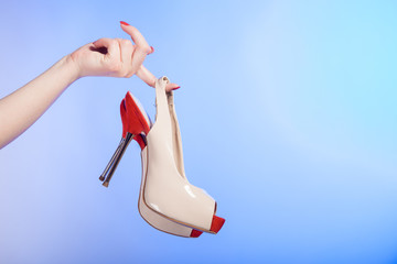 Red beige female shoes high heels in hands of woman on violet