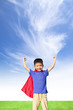 happy little boy imitate superhero and open arms with blue sky