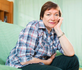 Stressed female pensioner on couch
