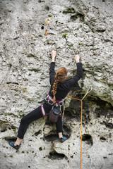 Young woman climbing rock.