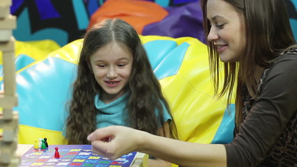 Smiling girl plays board game sister, family bonding, education