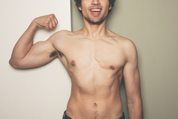 Young athletic man flexing his muscles
