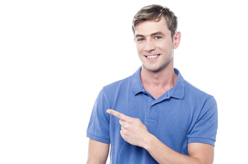 Cheerful man pointing his finger away