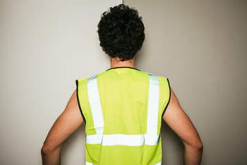 Rear view of builder in high visibility vest