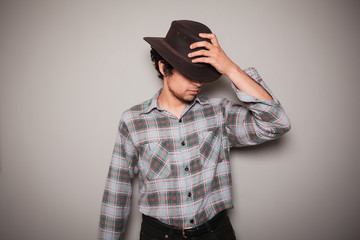 Young cowboy in plaid shirt against a grey wall