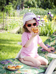 Little girl eating cake in the garden