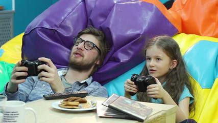 Man little girl playing video game, gaming habit, entertainment