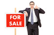 Male realtor standing by a for sale sign