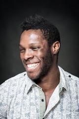 Smiling black man close up portrait against dark background.