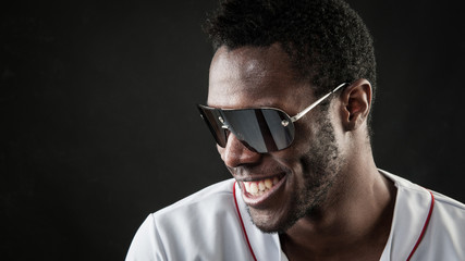 Laughing black man close up portrait with sunglasses against dar