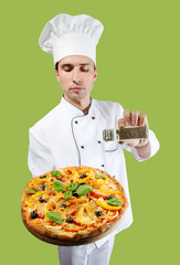 Studio portrait of a chef seasoning pizza with oregano