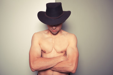 Shirtless young cowboy against dual colored background