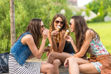 3 woman eating ice cream in town, sitting on a bench, laughing