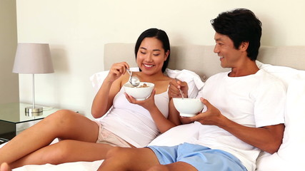 Couple eating bowls of cereal in bed