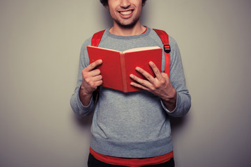 Happy young student with red book