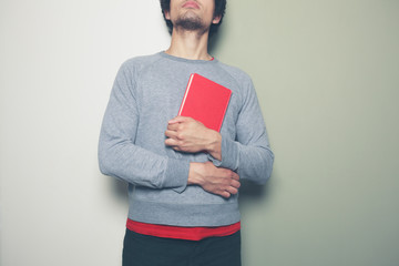 Young man with red book against split colored background