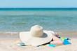 frau mit großem strohhut sonnt sich am strand