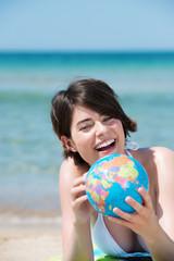 attraktive junge frau mit globus am strand