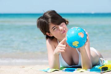 frau am strand zeigt auf globus