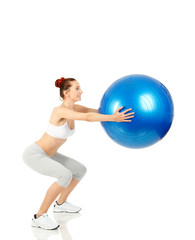 Fitness girl doing squats with pilates ball