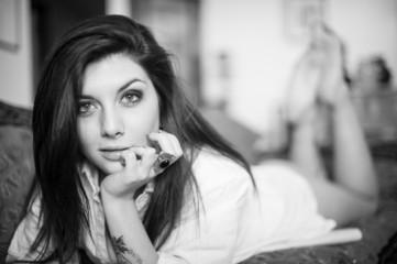 Sensual portrait of beautiful girl with tattoo lying on sofa. Bl