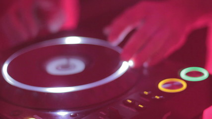 Dj's hands spinning platter on turntable in nightclub