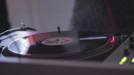 Dj changing the record at party, spinning vinyl in nightclub