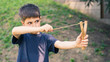 Child aiming with sling outdoors portrait.
