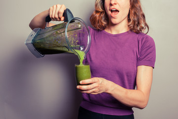 Young woman pouring a green smoothie
