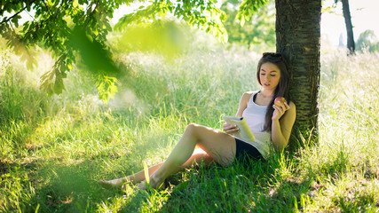 Beautiful young woman reading a book under a tree in the park.