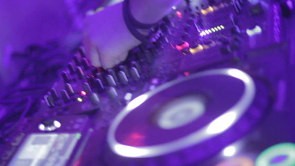 Dj's hands playing mix on sound board, platter spinning