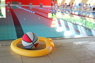 Schwimmnudel und Ball am Rand eines Sportbeckens