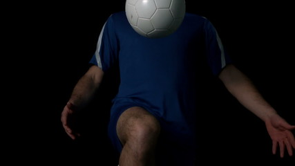 Footballer controlling the ball on black background