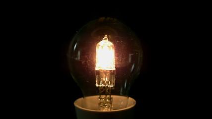 Light bulb turning on on black background