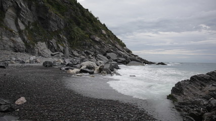 Deserted beach on the liguriysky coast in cloudy weather