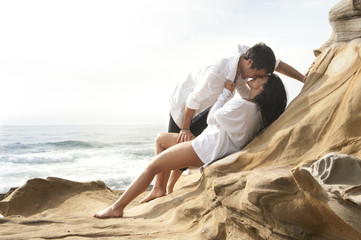 Young beautiful couple kissing on beach rocks wearing white