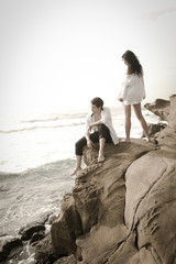 Young good looking couple on beach rocks wearing white