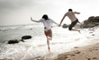 Young couple being playful on beach running into surf