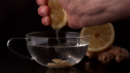 Hand squeezing lemon into cup of hot water and ginger