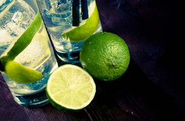 glasses with cocktail and ice with lime slice on wood background